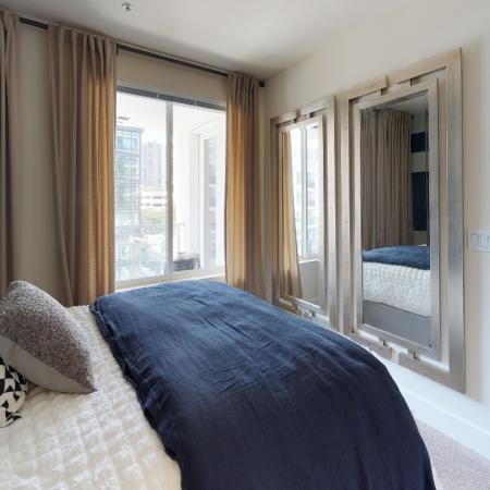 Bedroom with large windows and plush carpeting