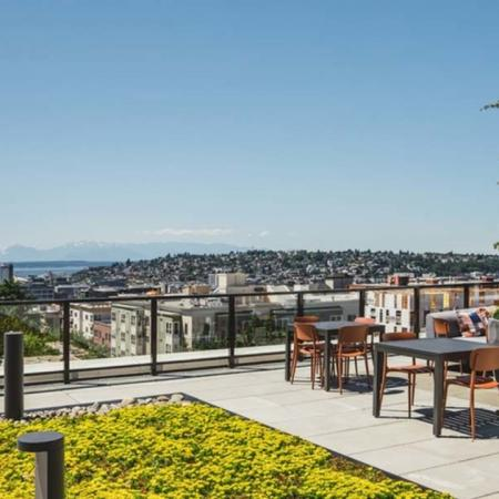 Rooftop dining area overlooking Seattle and mountain views at Modera Broadway apartments.