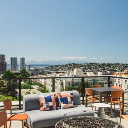 Lounge seating, firepit and dining table overlook Seattle and look towards the mountains at Modera Broadway apartments.