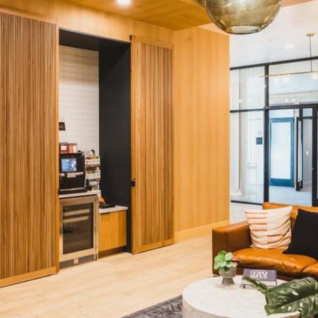 Coffee station in plush lounge with couches and library shelving in the lobby area at Modera Broadway apartments.