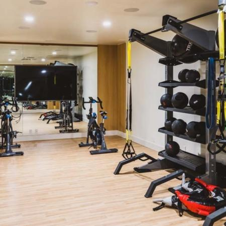 Yoga studio space with hardwood flooring, mirrors, ballet barre and TRX station at Modera Broadway apartments.