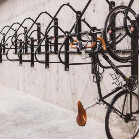 Hanging bikes on bike rack on a concrete wall at Modera Broadway apartments.