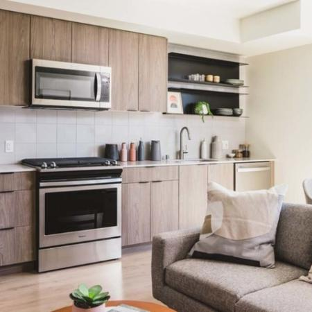 Galley-style kitchen in well-lit apartment home showing a stylish kitchen and living area at Modera Broadway Apartments.