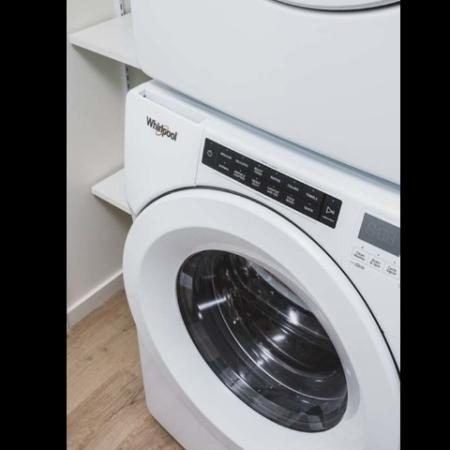 Close up of front-loading washing machine in apartment at Modera Broadway - Seattle.