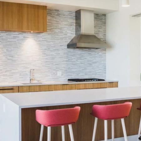 Demo kitchen with chef's island and barstool seating at Modera Broadway apartments.