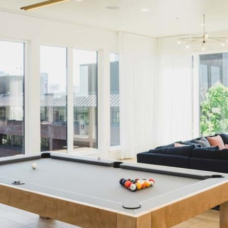 Light-filled room surrounded by large windows looking out on the city with lounge seating and a pool table