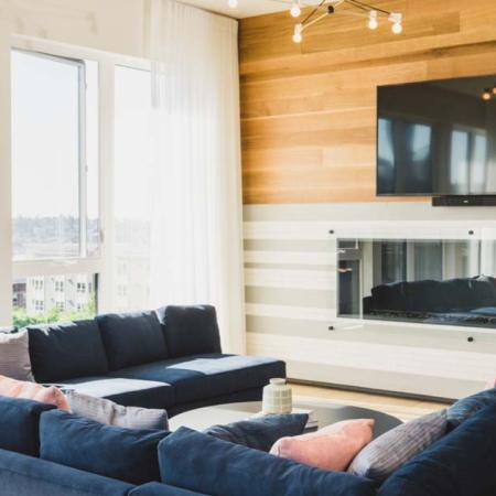 HDTV on the wall above a glass-walled fireplace with plush seating and city views at Modera Broadway apartments.