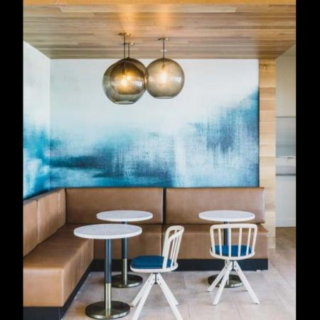 Banquet-seating nook with small tables and stylish lighting and artwork at Modera Broadway apartments.