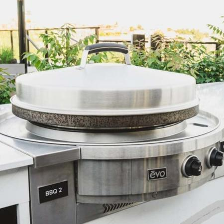 Closeup of EVO grill on rooftop with greenery in the background at Modera Broadway apartments.