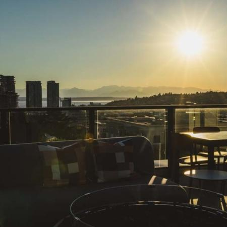 Rooftop deck lounge area with the sunset behind it over the mountains and the city at Modera Broadway apartments.
