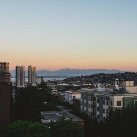Mountains in the distance illuminated by an orange sunset over the city of Seattle