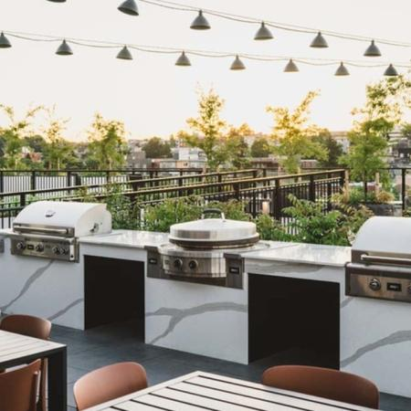 3 grilling stations and outdoor dining area under lights on a rooftop filled with greenery at Modera Broadway apartments.