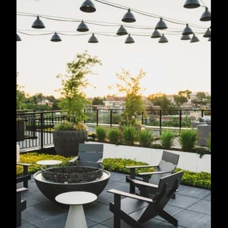 Adirondack chairs surround a round fire put under string lighting on the rooftop surrounded by greenery at Modera Broadway apartments.
