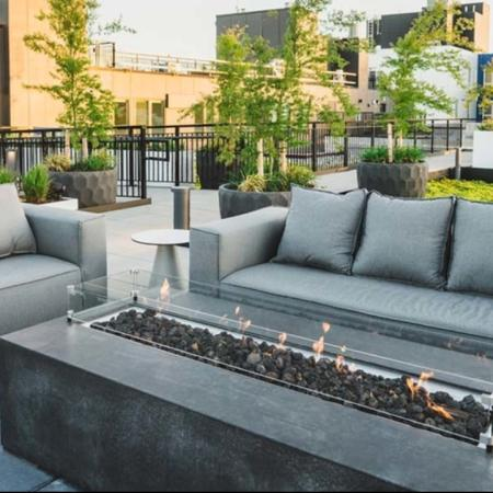 Fire pit lit up in front of 2 grey couches surrounded by greenery installations on the rooftop at Modera Broadway apartments.