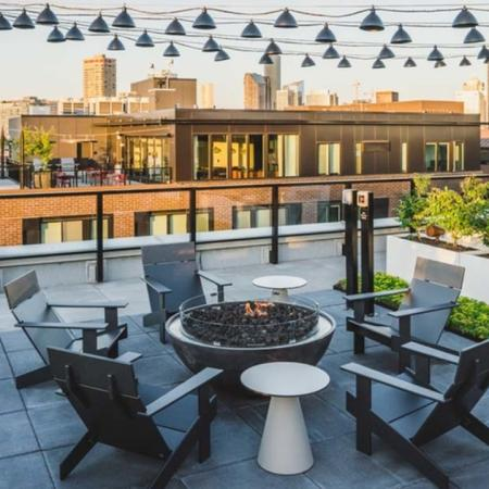 Rooftop fire pits and lounge seating under string lights at Modera Broadway Apartments.