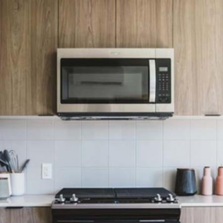 Stainless steel appliances in kitchen with white tile backsplash at Modera Broadway Apartments.