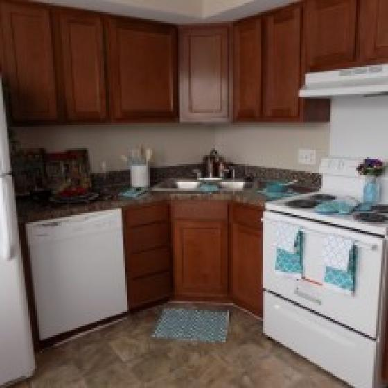 Newly remodeled kitchen with white appliances and cherry oak cabinets