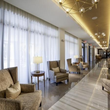 Lobby corridor with plush brown chairs.