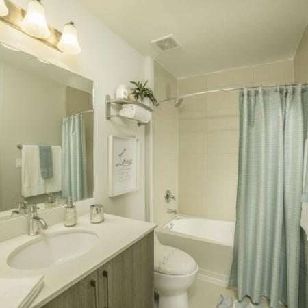 Bathroom with light blue shower curtain.