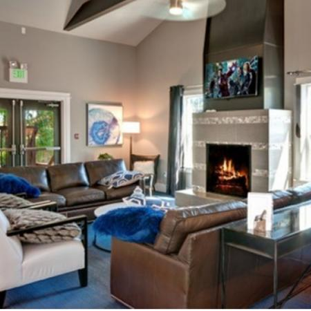 Clubhouse lobby with brown leather couches and fireplace.