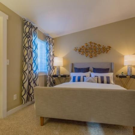 Bed with beige bedframe and blue accent pillows.