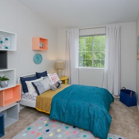Kids bedroom with bright colored cabinets and teal bedding.