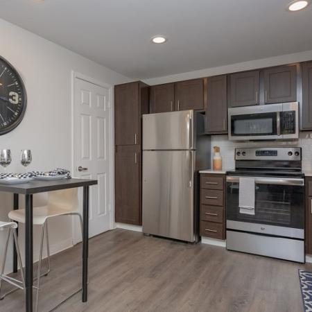 Kitchen with stainless appliances, and espresso cabinets.