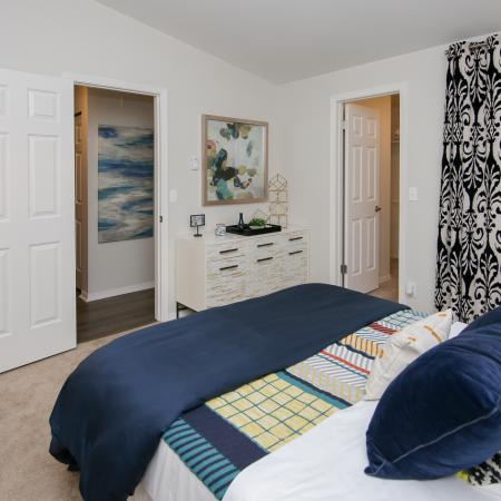 Bedroom with queen bed, and navy blue accent pillows.
