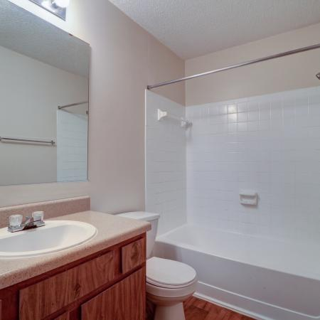 Oak Grove Apartments LLC, interior, bathroom, wood floor and cabinets, white tile, large mirror, sink, toilet, shower/tub