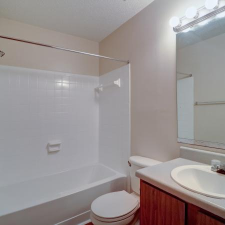 Oak Grove Apartments LLC, interior, bathroom, wood cabinet, large mirror, toilet, sink, shower/tub, white tile