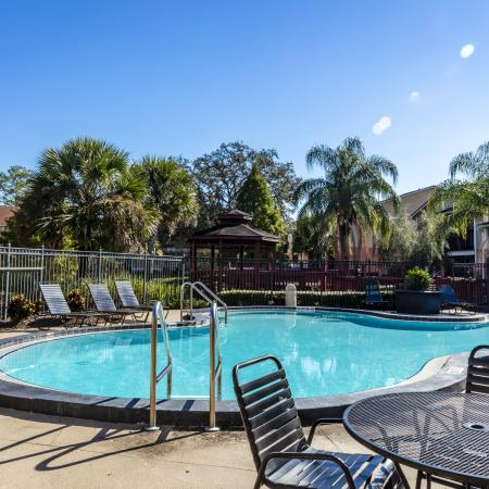 The Avenue Apartments, exterior, sparkling blue pool, clubhouse red brick, trees, outdoor seating tables and chairs