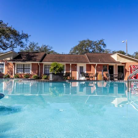 The Avenue Apartments, exterior, sparkling blue pool, clubhouse red brick, trees