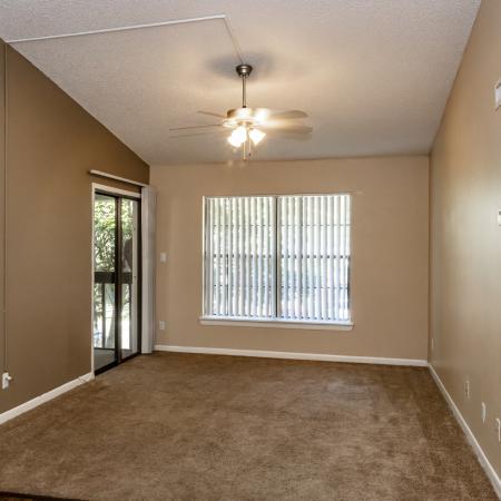 The Avenue Apartments, interior, living room, carpet, ceiling fan, large window, closet, sliding glass door to balcony