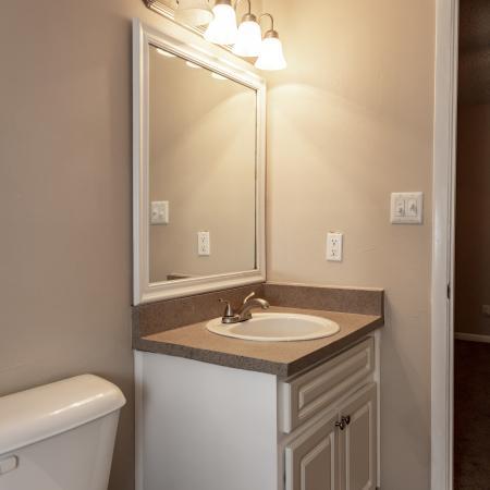 The Avenue Apartments, interior, bathroom wood floor, toilet, sink, white cabinet, large mirror, doorway