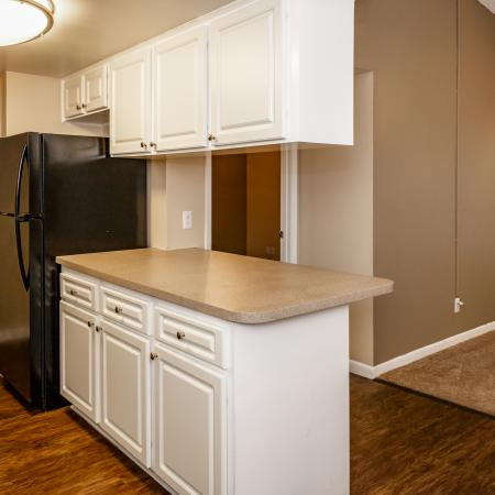 The Avenue Apartments, interior, kitchen, wood floor, breakfast bar counter, white cabinets, black refrigerator, pantry, carpeted living room, sliding glass doors.