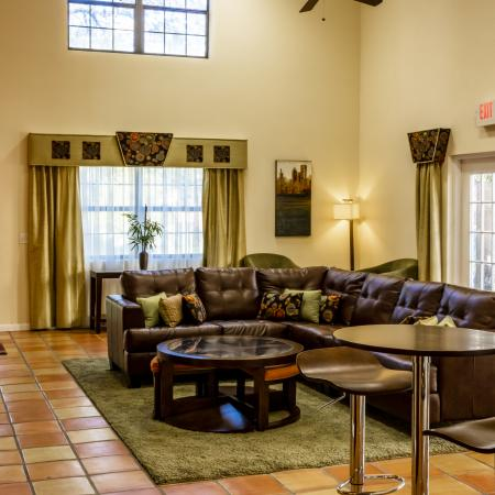 The Avenue Apartments, interior, common room, tile floor, leather sofa, high table and chairs, tv, coffee table, large windows, high ceilings, ceiling fan