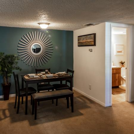 The Avenue Apartments, interior, dining room, carpeted, table for three with additional bench eating, green accent wall, doorway to bathroom, closet, kitchen breakfast bar