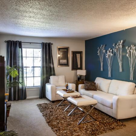 The Avenue Apartments, interior, living room, dark shelves, white couch, carpet, area rug, dark drapes, large windows, door to outside with blinds, green accent wall, lamp, wall decor