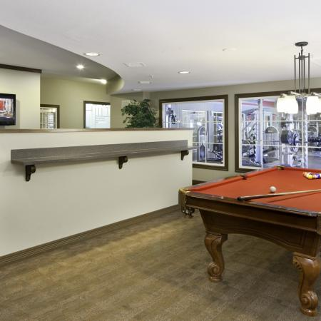 Fitness center and game room with pool table and TV at The Commons on Kinnear