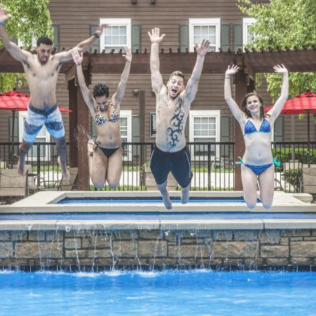 People jumping into outdoor pool | The Commons on Kinnear Apartments Near OSU