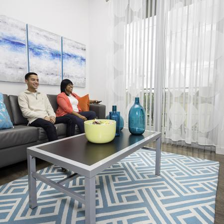 109 Tower, interior, living groom, man and woman sitting on gray couch, blue and white decor, large window, coffee table, wood floor