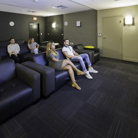 109 Tower, interior, theater room, large comfortable seating, dark furniture and carpet, two men and two women watching tv