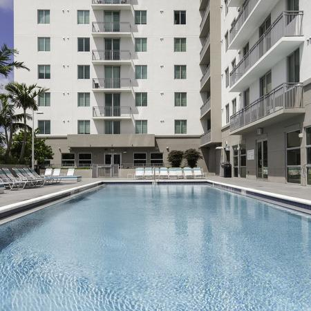 109 Tower, exterior, sparkling blue swimming pool, white high rise, balconies, trees
