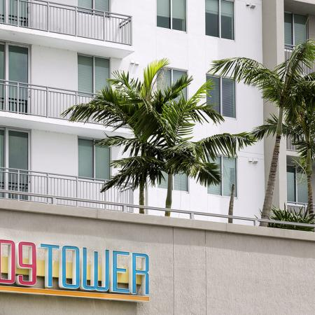 109 Tower, exterior, white and tan building, multi level, balconies, palm trees, buildings sign