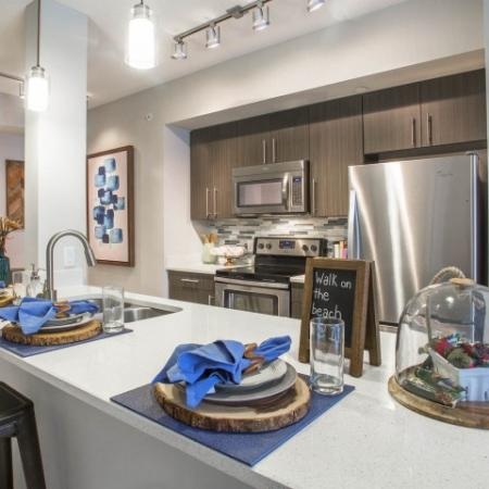 Boca City Walk Interior | Kitchen with table setting on island counter top | stainless steel apliances