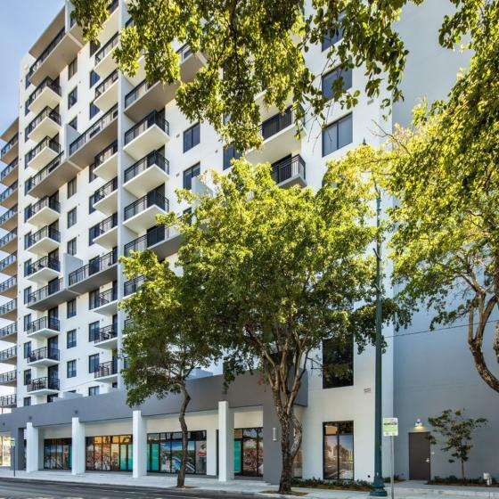Intown, exterior, tall white building, balconies, trees, street,