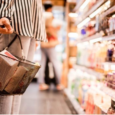 Person holding grocery basket in store