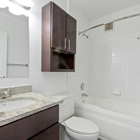 Bathroom, granite countertop, medicine cabinet over toilet and beautiful white tiled bath
