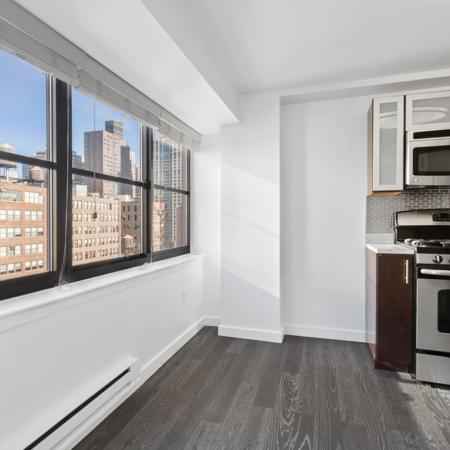 Large window view of city from Kitchen with stainless over
