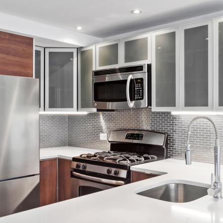 White counter tops in kitchen with Stainless appliances and bar sink